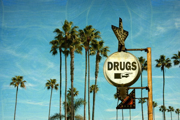 aged and worn vintage photo of drugs sign and palm trees