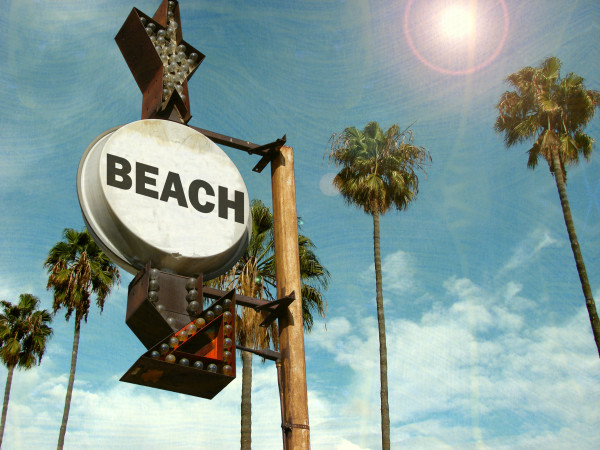aged and worn vintage photo of beach sign with palm trees