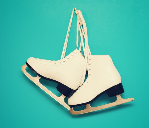 white ice skates for figure skating, hanging on a blue backgroun